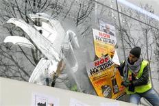 Manifestation des salariés de PSA Aulnay-sous-Bois devant le siège de Peugeot à Paris. Quatre syndicats se sont dits favorables mardi au projet d'accompagnement du plan social du groupe automobile qui prévoit 8.000 suppressions de postes et la fermeture de l'usine située en Seine-Saint-Denis. Mais le projet doit encore être soumis à l'approbation des salariés. /Photo prise le 12 février 2013/REUTERS/Philippe Wojazer
