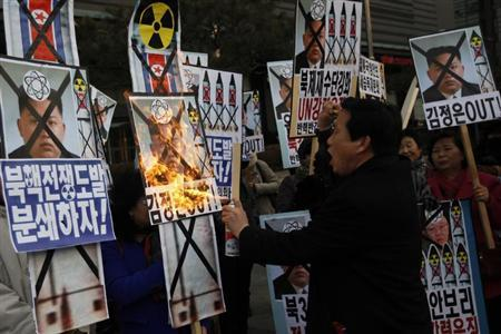 An activist from an anti-North Korea civic group burns a portrait of North's leader Kim Jong-un during a rally against North Korea's nuclear test near the U.S. embassy in central Seoul February 12, 2013. REUTERS/Kim Hong-Ji (SOUTH KOREA - Tags: CIVIL UNREST POLITICS) - RTR3DO91
