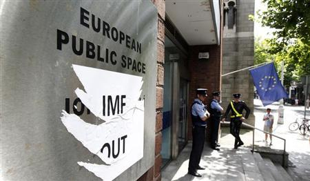 Members of the Gardai patrol outside the Dawson Street offices where the European Commission, European Central Bank and International Monetary Fund (IMF) held a joint news conference outlining Ireland's progress in meeting its targets as part of the EU/IMF bailout, in Dublin July 14, 2011. REUTERS/Cathal McNaughton