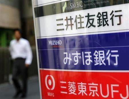 A man walks past signboards of Japan's three mega banks, Sumitomo Mitsui Banking Corporation (top), Mizuho Bank (C) and Bank of Tokyo-Mitsubishi UFJ, in Tokyo November 14, 2012. REUTERS/Toru Hanai (JAPAN - Tags: BUSINESS) - RTR3ADNM