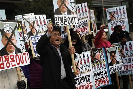 Activists from anti-North Korea civic group chant slogans during a rally against North Korea's nuclear test near the U.S. embassy in central Seoul February 12, 2013. North Korea conducted its third nuclear test on Tuesday in defiance of U.N. resolutions, angering the United States and Japan and prompting its only major ally, China, to call for calm. The placard (top C) reads, ''Kim Jong-un out!'' REUTERS/Kim Hong-Ji (SOUTH KOREA - Tags: CIVIL UNREST POLITICS) - RTR3DO8X