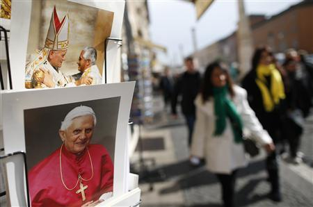 Tourists walk past pictures of Pope Benedict XVI displayed in a shop in Rome February 12, 2013. REUTERS/Tony Gentile