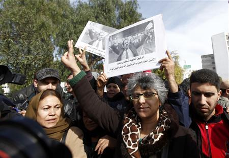 Basma Beliad (C), the widow of assassinated leftist politician Chokri Belaid, carries a poster of her husband as she's surrounded by journalists, during a demonstration calling for Prime Minister Hamadi Jebali and his cabinet to step down, next to the National Constituent Assembly in Tunis, February 11, 2013. REUTERS/Anis Mili