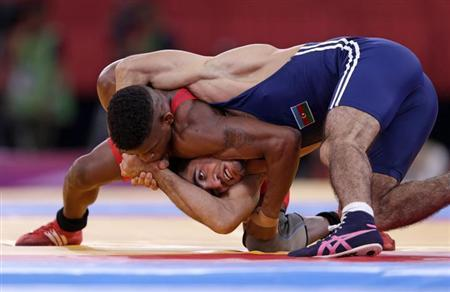 Cuba's Livan Lopez Azcuy (in red) fights with Azerbaijan's Jabrayil Hasanov for the bronze medal of the Men's 66Kg Freestyle wrestling at the ExCel venue during the London 2012 Olympic Games August 12, 2012. REUTERS/Toru Hanai/Files