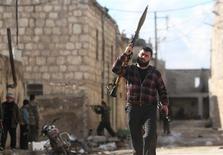 Tras casi dos años de conflicto armado en Siria, el número de muertos está cerca de 70.000 y son los civiles quienes pagan el precio de la falta de acción por parte del Consejo de Seguridad de Naciones Unidas ante el enfrentamiento, dijo el martes la jefa de derechos humanos del organismo. En la imagen, un combatiente del Ejército Libre Sirio sostiene un lanzacohetes mientras otro dispara su arma al fondo durante enfrentamientos con fuerzas leales al presidente Bashar el Asad en el frente en Alepo, el 12 de febrero de 2013. REUTERS/Muzaffar Salman
