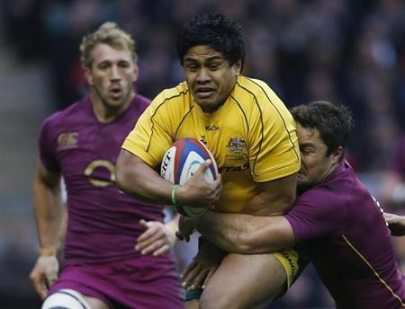 Australia's Ben Tapuai (C) is tackled by England's Brad Barritt during their international Rugby Union match at Twickenham stadium in London November 17, 2012. REUTERS/Eddie Keogh