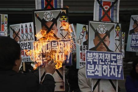 An activist from an anti-North Korea civic group burns a portrait of North's leader Kim Jong-un during a rally against North Korea's nuclear test near the U.S. embassy in central Seoul February 12, 2013. REUTERS/Kim Hong-Ji