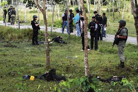 Security personnel investigate around bodies of insurgents at the site of an attack on an army base in the troubled southern province of Narathiwat February 13, 2013. REUTERS/Surapan Boonthanom