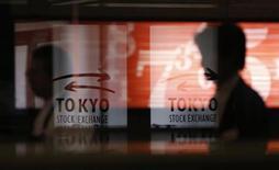 El Índice Nikkei cayó el miércoles por toma de beneficios en las empresas exportadoras, en medio de una subida del yen, mientras que la compañía de juegos de azar, Gree Inc, registró una pronunciada caída por el recorte de su previsión de beneficio anual. En la imagen, unos hombres pasan junto a unos logos en la bolsa de Tokio, el 6 de febrero de 2013. REUTERS/Toru Hanai