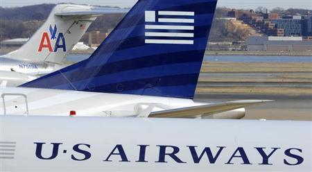 A view of two US Airways Express planes next to an American Airlines plane (background) at the Ronald Reagan Washington National Airport in Arlington County, Virginia, February 10, 2013, as negotiations continue this week between parent companies US Airways Group Inc and AMR Corp on a possible $11 billion merger, creating what would be the world's largest airline. REUTERS/Mike Theiler
