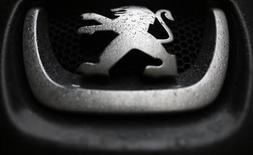 Логотип Peugeot на автомобиле компании в Париже 9 января 2013 года. Чистый убыток PSA Peugeot Citroen в 2012 году составил 5 миллиардов евро из-за бухгалтерских списаний, и компания обещает масштабное снижение издержек на фоне продолжающегося сокращения европейского авторынка. REUTERS/Christian Hartmann