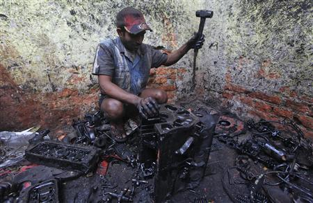 A worker uses a hammer to break apart a used truck engine at a small scale factory in Kolkata February 12, 2013. REUTERS/Rupak De Chowdhuri