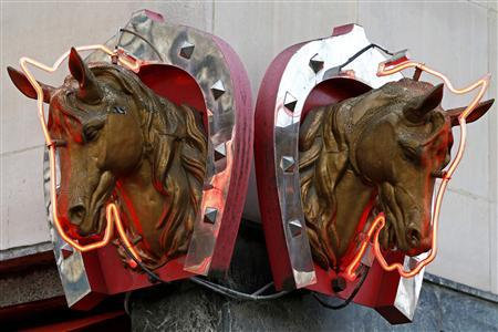 Metal horse heads outlined with neon lights are seen above a horsemeat butcher shop in Paris in this February 11, 2013 file picture. REUTERS/Charles Platiau/Files