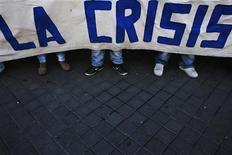 """BBVA cree que la recesión de la economía española se moderará este año a la vez que mejorará el saldo de su déficit fiscal, aunque las previsiones del segundo banco español todavía están lejos de contemplar el escenario más optimista del Gobierno. En la imagen, varios manifestantes con un cartel en el que se lee """"La crisis"""" en Madrid el 7 de febrero de 2013. REUTERS/Susana Vera"""