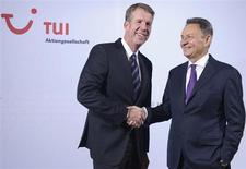 Michael Frenzel (R), outgoing CEO of German travel company TUI AG, shakes hands with his successor Friedrich Joussen for the media before the annual general shareholder meeting in Hanover, February 13, 2013. Joussen, who will take the top job at TUI following the AGM, said on Wednesday he wanted to make the company more capital and cost efficient. REUTERS/Fabian Bimmer (GERMANY - Tags: BUSINESS) - RTR3DQ4U