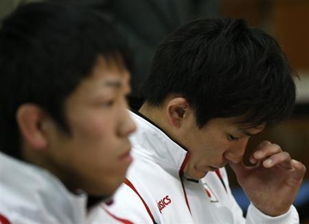 London 2012 Olympic Games bronze medal wrestler Shinichi Yumoto (R) of Japan, along with London 2012 Olympic Games gold medal wrestler Tatsuhiro Yonemitsu, reacts during a news conference in Tokyo February 13, 2013. REUTERS/Toru Hanai