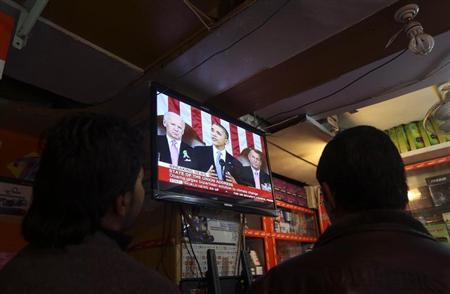 Afghan men watch a television broadcast of U.S. President Barack Obama delivering his State of the Union speech, in Kabul February 13, 2013. REUTERS/Omar Sobhani (AFGHANISTAN - Tags: POLITICS MILITARY) - RTR3DPZ3
