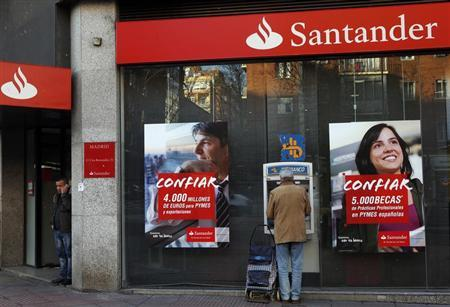 A man uses an ATM machine as another talks on the phone outside a Santander bank branch in Madrid January 31, 2013. REUTERS/Susana Vera