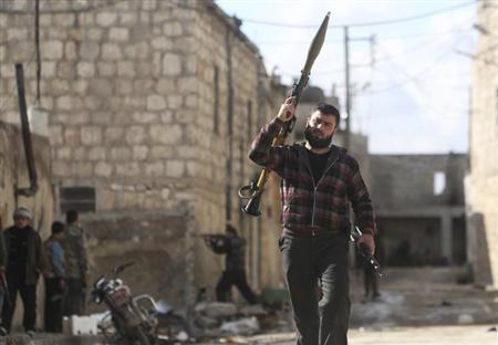 A Free Syrian Army fighter holds an RPG launcher as another fighter fires his weapon during clashes with forces loyal to Syria's President Bashar al-Assad on the frontline of Aleppo's Sheikh Saeed neighbourhood February 12, 2013. REUTERS/Muzaffar Salman