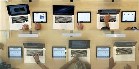 Customers look at MacBook Pros, during the official opening of the largest Apple shop in southern Europe, at Passeig de Gracia in Barcelona July 28, 2012. REUTERS/Albert Gea/Files