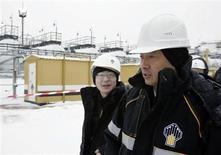 Член руководства совместного предприятия Роснефти и Китая Жай Хуйхай (справа) идет по территории нефтяного месторождения Гремихинское в уральских горах к востоку от Ижевска 7 декабря 2007 года. Роснефть ведет переговоры с Китаем о предоставлении кредита на сумму до $30 миллиардов и готова в обмен удвоить поставки нефти в страну, сообщили Рейтер четыре источника в отрасли. REUTERS/Sergei Karpukhin