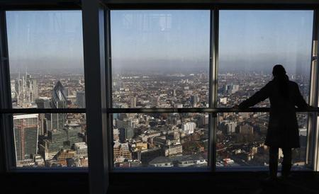 A woman looks out at the financial district from a window in The View gallery at the Shard, western Europe's tallest building, in London January 9, 2013. REUTERS/Luke Macgregor