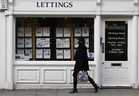 A woman walks past an estate agent in Chelsea, London February 7, 2013. REUTERS/Stefan Wermuth