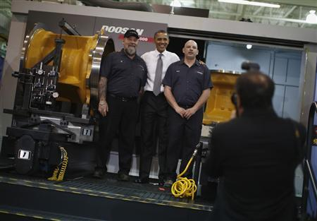 U.S. President Barack Obama poses for a picture with workers as he tours Linamar Corporation that manufactures parts for the truck industry in Arden, North Carolina, February 13, 2013. REUTERS/Jason Reed