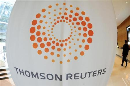 A man walks near a Thomson Reuters logo at the Thomson Reuters building in Canary Wharf in east London May 7, 2009. REUTERS/Toby Melville/Files