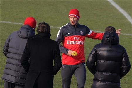 Paris Saint Germain's soccer player David Beckham (2ndR) speaks with Paris St-Germain sports director Leonardo (2ndL) and coach Carlo Ancelotti (L) during his first training session with PSG squad at the Camp des Loges training center in Saint-Germain-en-Laye, near Paris, February 13, 2013. REUTERS/Gonzalo Fuentes