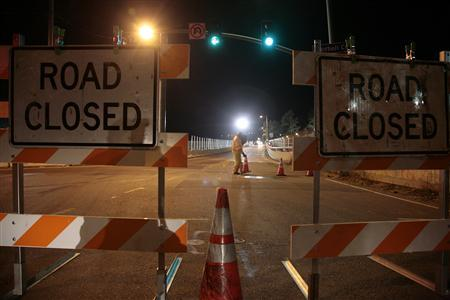 A worker places traffic cones on the road as the Mulholland bridge is closed over the 405 freeway in Los Angeles, California July 15, 2011. REUTERS/Jason Redmond