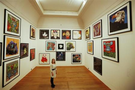 Gallery employee Maddy Adeane poses with Andy Warhol images at the Dulwich Picture Gallery in London June 19, 2012. REUTERS/Luke MacGregor