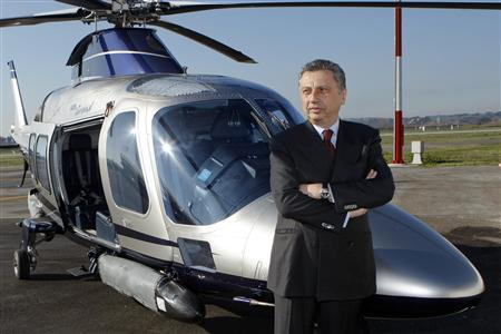 Finmeccanica Chairman and Chief Executive Officer Giuseppe Orsi poses next to a helicopter during the opening ceremony of the new Terminal of Vertiporto dell'Urbe in Rome in this January 19, 2009 file photo. Orsi was arrested on February 12, 2013 in a probe over allegations of corruption in an Indian helicopter deal. REUTERS/Remo Casilli/Files