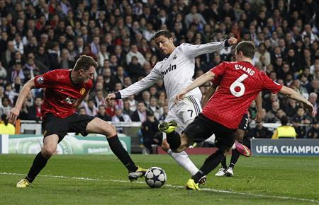Manchester United's Phil Jones (L) and Jonny Evans stop Real Madrid's Cristiano Ronaldo from scoring during their Champions League soccer match at Santiago Bernabeu stadium in Madrid February 13, 2013. REUTERS/Paul Hanna