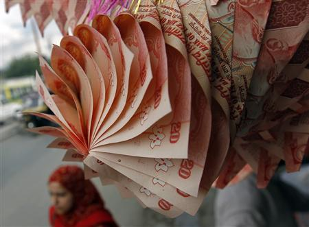 A Kashmiri woman walks under a garland made of Indian currency notes on display at a market in Srinagar September 3, 2012. . REUTERS/Fayaz Kabli