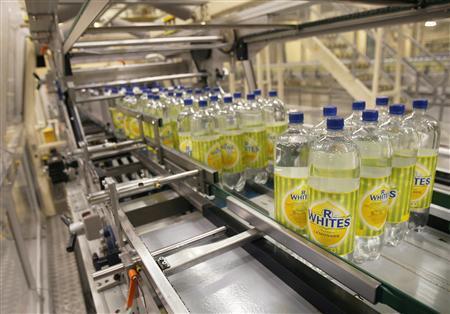 Bottles of R Whites lemonade, made by soft drinks company Britvic, sit on a conveyor belt at Britvic's bottling plant in London March 25, 2009. REUTERS/Luke MacGregor