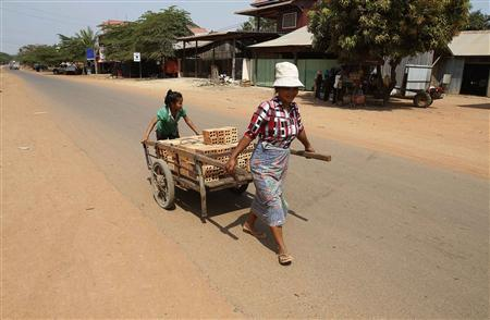 A woman and her daughter transport a cart of bricks at the Rovieng District in Preah Vihear province February 10, 2013. The remote district of Rovieng was once a battleground between Cambodian government troops and Pol Pot's genocidal Khmer Rouge. Unexploded bombs still lurk in its fields and forests. So does something more desirable - iron ore - and supposedly in such huge quantities two Chinese companies have an $11-billion plan to extract it. Their proposal - a steel plant and seaport linked by a 404-km (251-mile) railroad - has alarmed environmentalists, mystified mining and transport experts, and bolstered Cambodia's reputation as an agent for Chinese expansionism in a region where the United States is increasingly competing for influence. Picture taken February 10, 2013. REUTERS/Samrang Pring