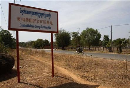 A man rides a motorcycle past a signboard for the Cambodia Iron Group at the Rovieng District in Preah Vihear province February 10, 2013. REUTERS/Samrang Pring