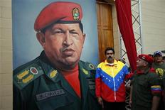 Venezuelan Vice President Nicolas Maduro (C) and National Assembly President Diosdado Cabello (R) stand next to a painting of Venezuelan President Hugo Chavez as they attend the commemoration of the 21st anniversary of Chavez's attempted cuop d'etat in Caracas February 4, 2013. REUTERS/Jorge Silva