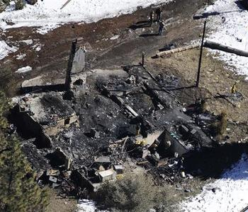 Authorities stand at a burnt out cabin near Angelus Oaks, California February 13, 2013, where police believe they engaged in a shootout with fugitive former Los Angeles police officer Christopher Dorner on Tuesday. REUTERS/Gene Blevins