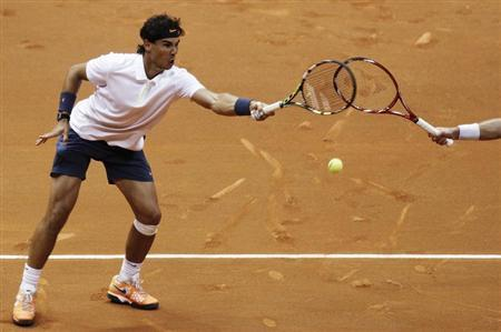 Rafael Nadal (L) of Spain hits a return next to David Nalbandian of Argentina during their men's doubles match against Spain's Pablo Andujar and his compatriot Guillermo Garcia-Lopez at the Brazil Open tennis tournament in Sao Paulo February 12, 2013. REUTERS/Nacho Doce