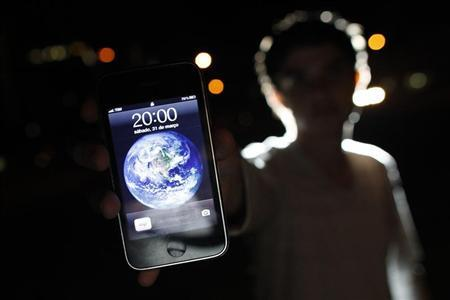 A man poses with an iPhone during Earth Hour in the center of Brasilia March 31, 2012. REUTERS/Ueslei Marcelino