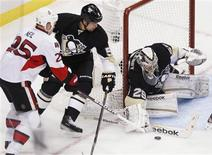 Pittsburgh Penguins goalie Marc-Andre Fleury (29) blocks a shot by Otttawa Senators' Chris Neil (25) as Penguins' Deryk Engelland (5) tries to defend in the third period of their NHL hockey game in Pittsburgh, Pennsylvania, February 13, 2013. REUTERS/Jason Cohn