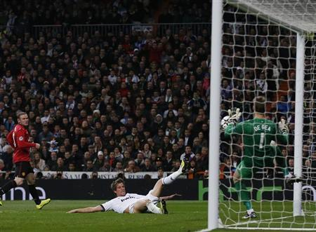 Manchester United's goalkeeper David De Gea (R) saves a shot by Real Madrid's Fabio Coentrao during their Champions League soccer match at Santiago Bernabeu stadium in Madrid February 13, 2013. REUTERS/Juan Medina