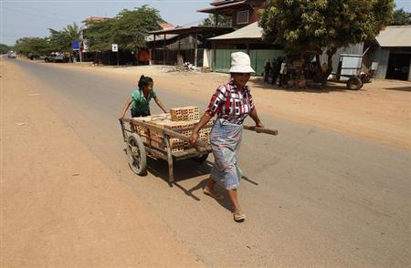 A woman and her daughter transport a cart of bricks at the Rovieng District in Preah Vihear province February 10, 2013. REUTERS/Samrang Pring