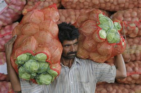 A man carries sacks filled with cabbages at a wholesale vegetable market on the outskirts of Jammu September 14, 2011. REUTERS/Mukesh Gupta/Files
