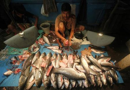 A vendor cuts fish at his stall at a wholesale fish market in Kolkata July 16, 2012. REUTERS/Rupak De Chowdhuri/Files