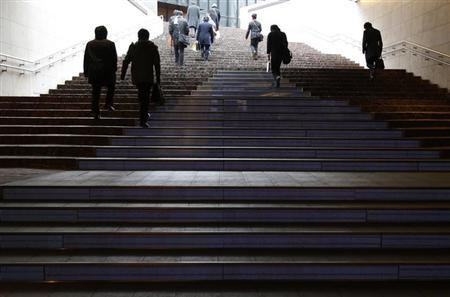 Passersby walk up a flight of stairs at a station in Tokyo February 14, 2013. Japan's economy contracted for the third consecutive quarter in October-December, showing the country is struggling to escape from a mild recession and adding weight to the new government's push for radical policy steps to revive growth. REUTERS/Yuya Shino (JAPAN - Tags: BUSINESS)