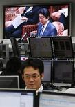 A television screen shows Japan's Prime Minister Shinzo Abe attending the lower house budget committee session at the parliament, behind an employee of a foreign exchange company in Tokyo February 12, 2013. The yen hovered near fresh lows against the dollar and Tokyo stocks jumped back near a 33-month high on Tuesday after markets took comments from a U.S. official as giving Japan the green light to pursue policies that weaken the yen as long as they help beat deflation. REUTERS/Toru Hanai (JAPAN - Tags: BUSINESS POLITICS)