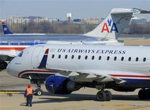 Los consejos de administración de AMR Corp y US Airways Group se reunieron el miércoles para aprobar una fusión que crearía la mayor aerolínea del mundo con un valor de mercado esperado de unos 11.000 millones de dólares, dijeron personas familiarizadas con el asunto. En la imagen, un avión de US Airways y otro de American Airlines en el aeropuerto Ronald Reagan en Arlington County, Virginia, el 10 de febrero de 2013. REUTERS/Mike Theiler